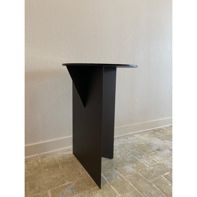 Contemporary side table with black glass top and iron base. Sleek and sexy, would work in a tight space, and any interior.