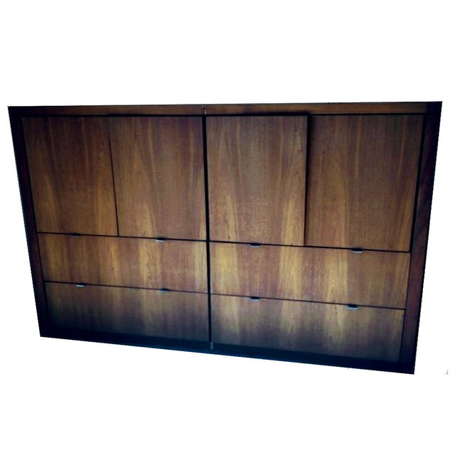 DESIGN: A 1970's double wide unusual storage cabinet comprised of two conjoined identical walnut veneered bureaus that...