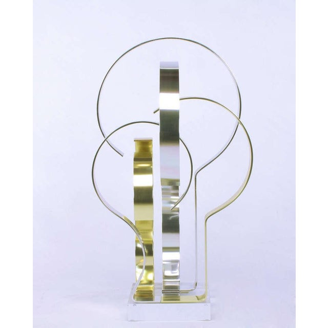 """Brass effect & natural polished aluminum sculpture mounted on Lucite titled """"Misergo"""" by American metal sculptor Dan..."""