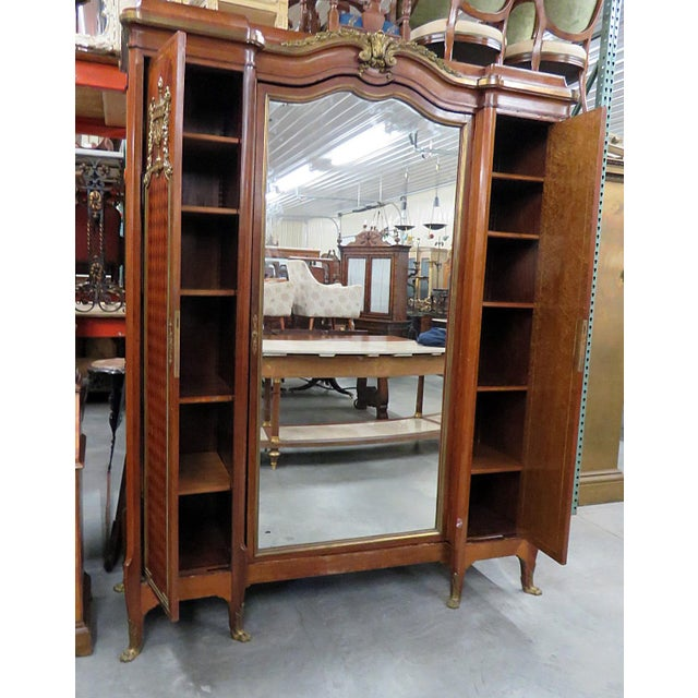 Regency style inlaid wardrobe with bronze mounts, attributed to Forest. Each of the 2 side doors contain 5 shelves, and...