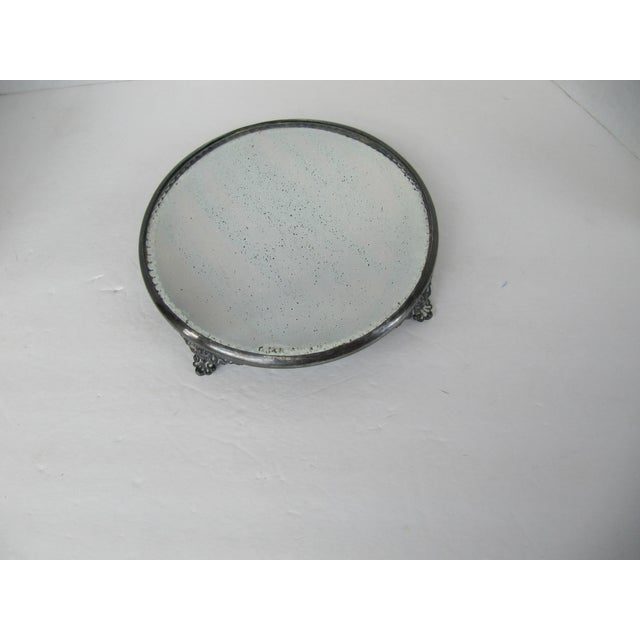 Vintage round silver-plate footed tray with beveled mirror insert. Unique piece to use on your vanity. This piece could...