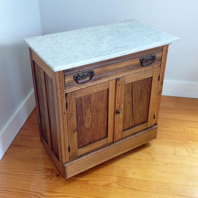 Beautiful antique American oak washstand vanity with attached white carrera marble top. The aged patina is gorgeous and...