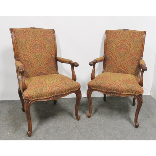 A pair of Louis XV style chairs made by EJ Victor, hand-carved floral accents, walnut frame, and paisley style fabric....