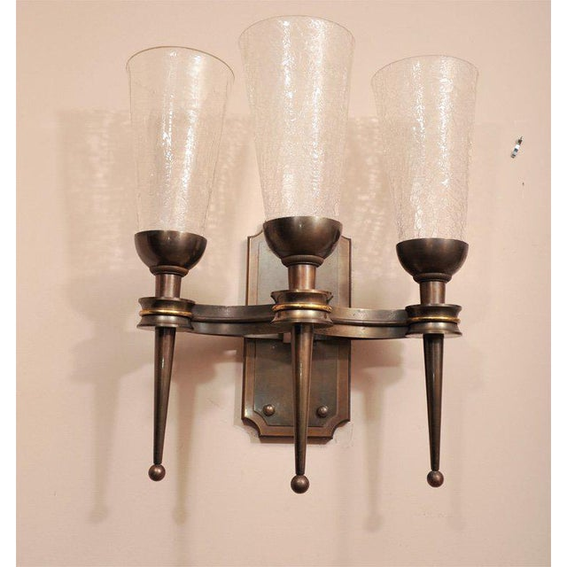 A pair of 1940s wall sconces, in cast bronze, each sconce featuring three uplight shades in crackled glass.