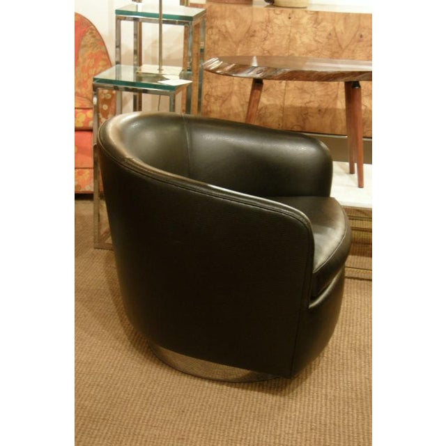 A pair of chic barrel back swivel and tilt lounge chairs upholstered in black leather raised on a round chromed steel...