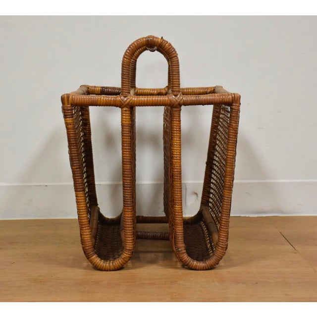 "This bent rattan wrapped magazine rack has two compartments and woven rattan sides. 14"" wide. 18"" deep. 18.5"" tall."