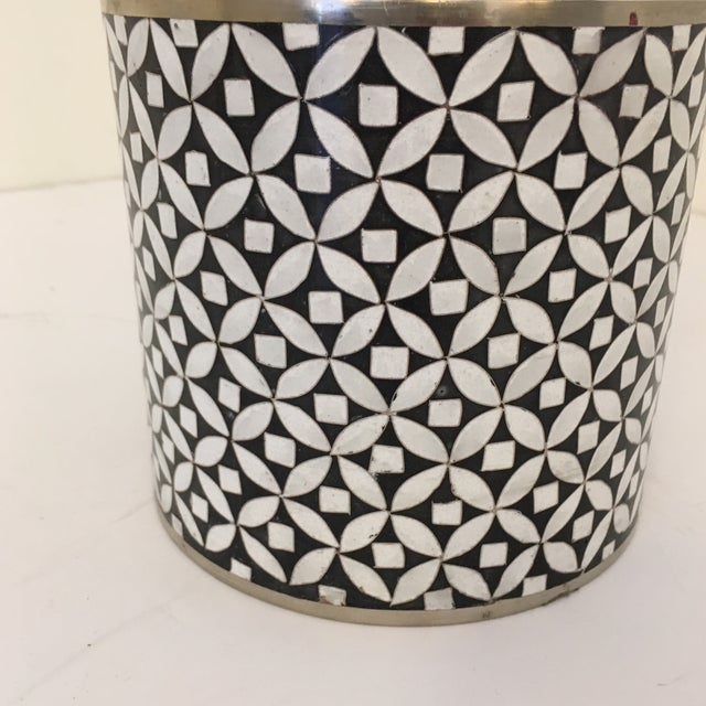 This contemporary cloisonné jar and a black and white pattern On metal.