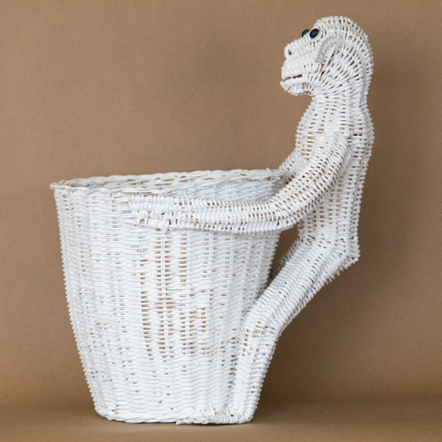 1970s wicker monkey with blue glass eyes hugging a waste basket or planter by Mario Lopez Torres. The wicker is painted...