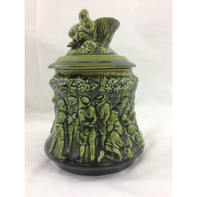Vibrant green tobacco jar with a lively party scene, including a musician on the lid. Majolica marking on bottom. Minor...