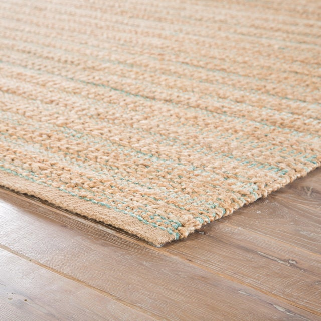 A natural area rug with a contemporary touch, this cotton-backed layer's golden beige tone and hints of green and pale...