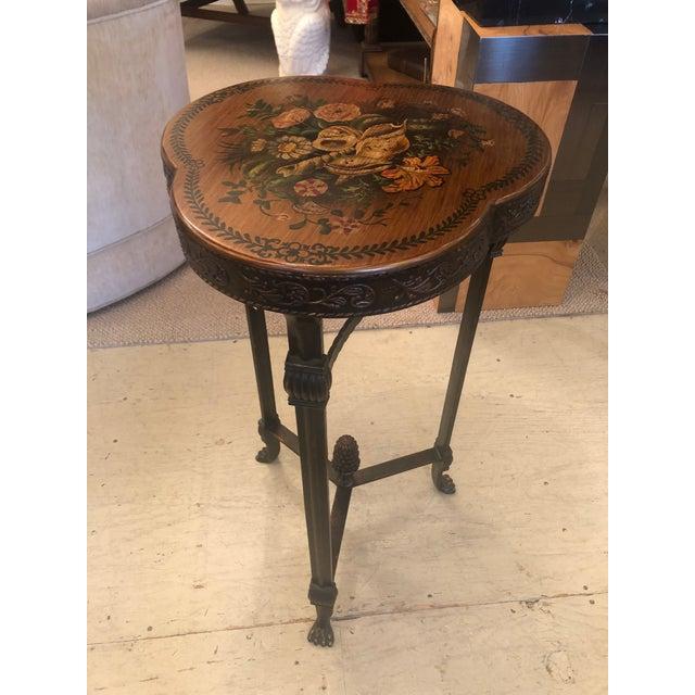 Shamrock shaped handsome end table having floral decoration on top, decorative embossed bronze finished metal on the...