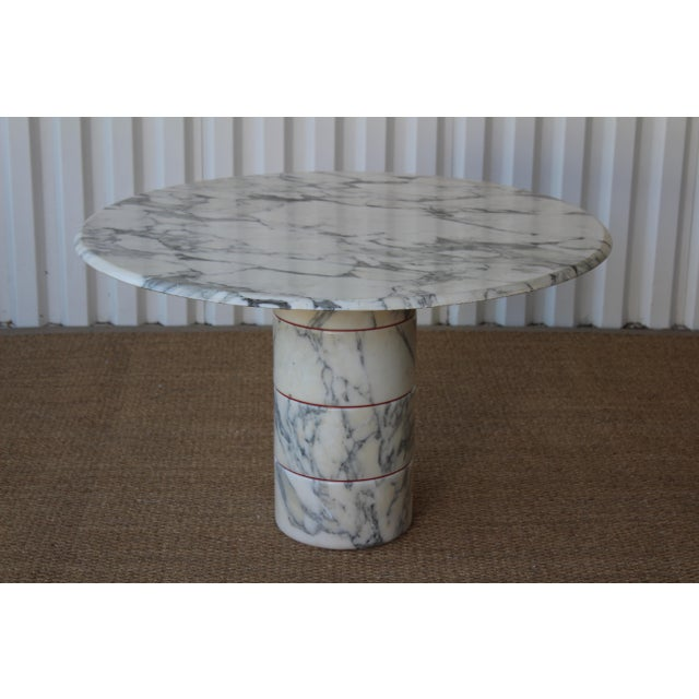Vintage 1970s arabescato carrara Italian marble dining table. Features a stacked marble base with red enamel steel plates...