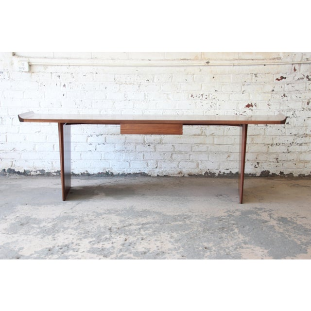 Offering an extraordinary curved top minimalist executive desk by Harvey Probber. This piece has been newly restored and...