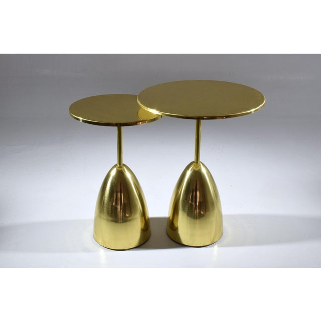 A set of two contemporary handcrafted guéridon nesting side or end tables composed of a solid polished gold brass...