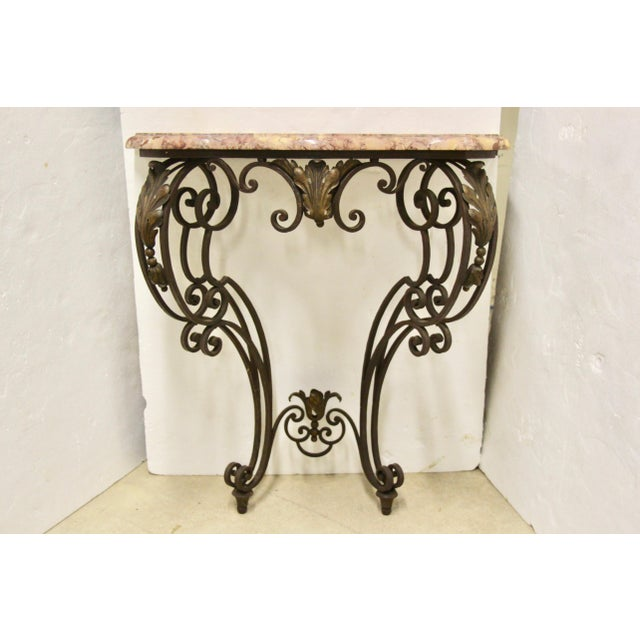 Lovely and unique wall mounted demilune console table. Features a custom cut stone top with beveled edge and wrought iron...