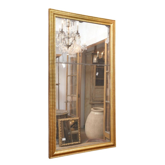Louis XVI Gilded Mirror: two tones of gilding adorn frame surrounding a bipartite mirror plate. Mirror's reflection is...