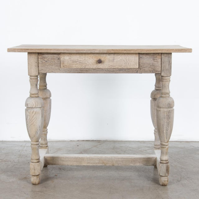 A bleached oak side table from France, circa 1900. Large turned legs support a simple wood frame, crafted from thick slabs...