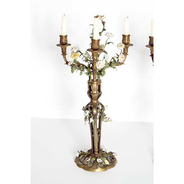 A whimsical pair of French gilt bronze candelabra with a filigree base and stems. Each candlestick has three arms. Applied...