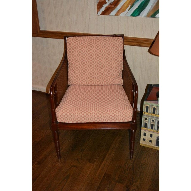 A pair of cane and mahogany sheraton/ bamboo style armchairs by Hickory Chair Company. This pair of chairs is in a faux...