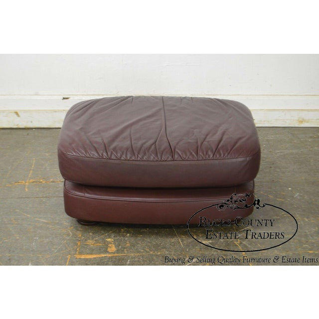 High quality genuine leather upholstered ottoman, with solid wood turned feet.~ Reddish/brown colored leather. Store...