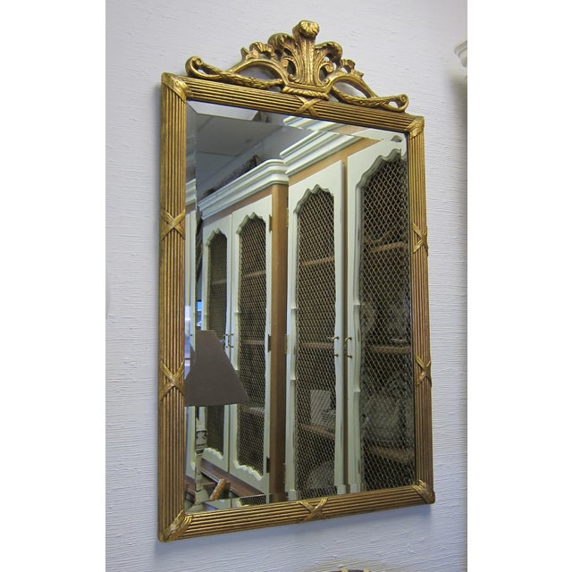 Prince of Wales Gilded Mirror. A beveled edge mirror in a gilt reed and ribbon wood carved frame topped with the Prince of...