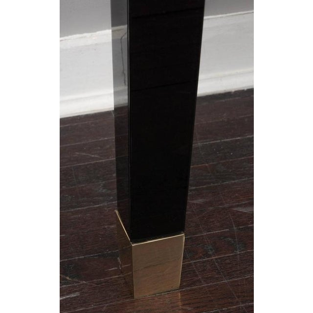 Black glass wall mount console table with brass sabot's.