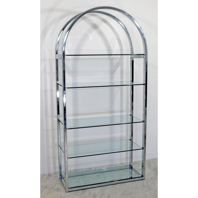 For your consideration is an incredible and unique, curved chrome étagère shelving unit, with five glass shelves, by Milo...