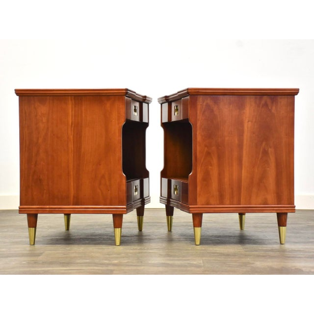 A pair of mid century modern cherry nightstands with brass drawer pulls and ferrules by John Widdicomb. Professionally...