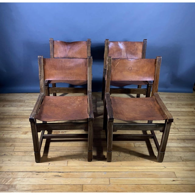 An exceptional set of four 1940s French country dining chairs with that perfect amount of patina. Dark cognac stained...