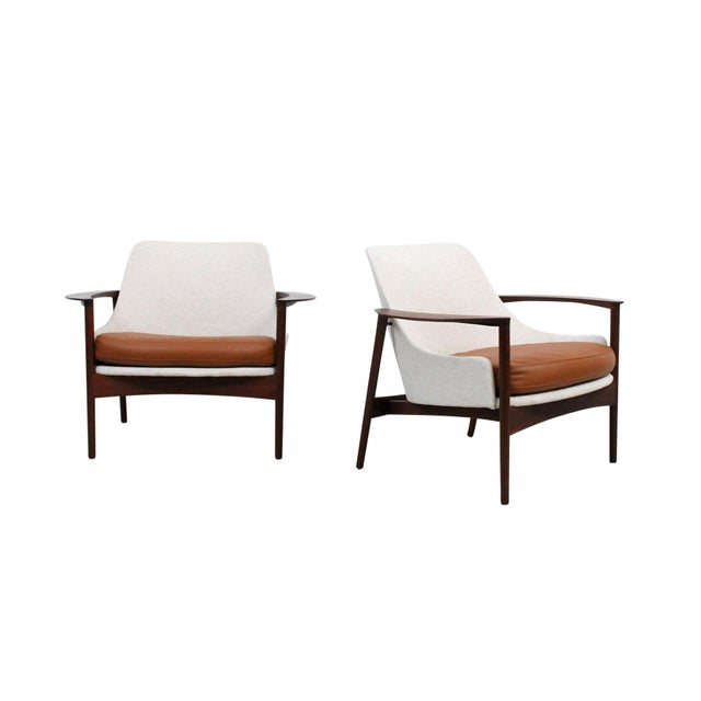 Pair of rare lounge chairs by Ib Kofod-Larsen for Selig. Sculptural walnut frames with leather seat cushions reminiscent...