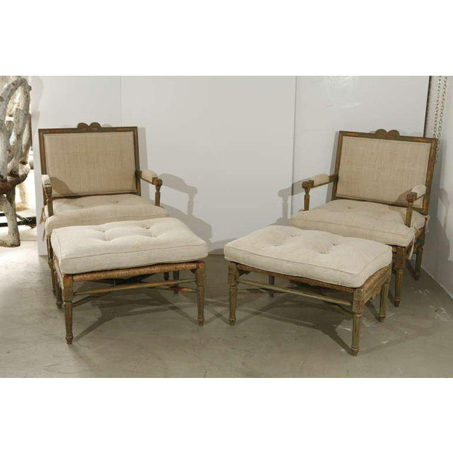 A pair of Louis XIV-style pailles fauteuils with footstools. Painted, carved wood framework, with woven straw bottoms and...