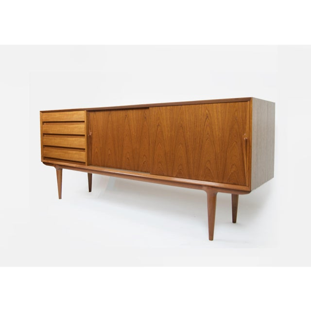 Gorgeous teak credenza designed by Gunni Omann For Omann Jun Model 18. Featuring a hand sculpted knife edge handles on...