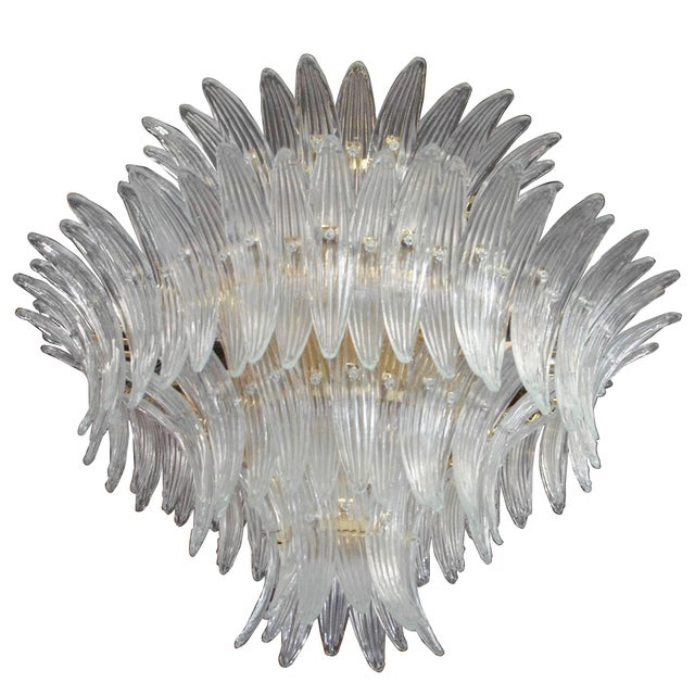 Italian Palmette chandelier shown in clear Murano glass leaves arranged on four tiers and gold-plated metal frame, in the...
