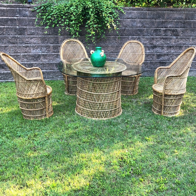 Beautiful collection of for wicker peacock chairs with a rare wicker table and original glass. Would look beautiful...