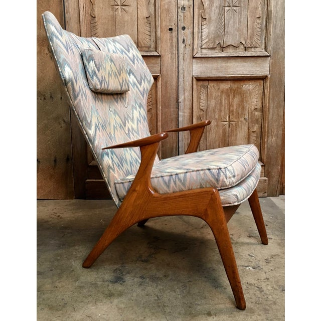 Very comfortable Danish modern lounge chair with the curved high back in original flame stitch fabric and solid oak frame