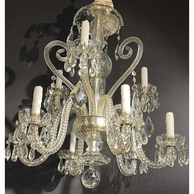 A fine cut crystal Venetian style chandelier having nine lighted arms on a central crystal column center support. The...