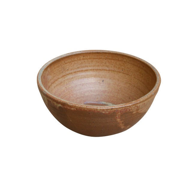 A simple round stoneware bowl in neutral brown and caramel colors. Underneath is pressed a symbolic maker's mark.