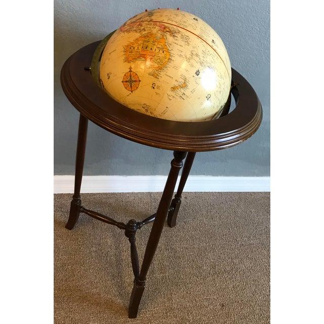 Stunning vintage globe on a mahogany wood table.