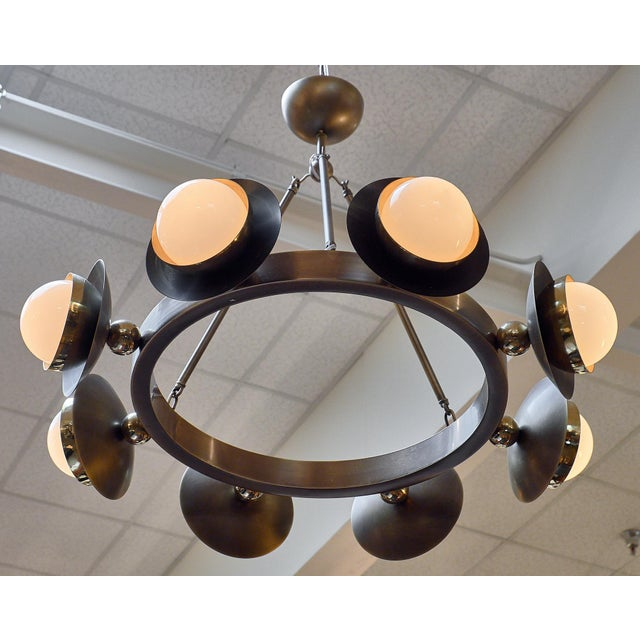 Murano Glass and bronze chandelier featuring hand-blown glass globes. Each globe is held within a brass and bronze...