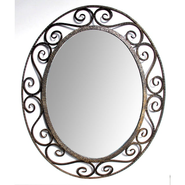 A hand-crafted French art deco openwork iron oval mirror in the style of Edgar Brandt; the oval plate within a punched...