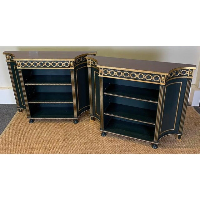 A small and elegant pair of mid 20th C. carved and paint decorated Regency style bookcases made for Colefax and Fowler in...