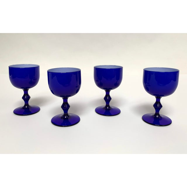Set of four blue cocktail or wine goblets with fused white glass interior from Italian glass designer and manufacturer...