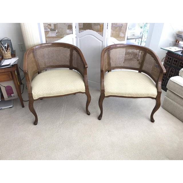 Offered as a pair, these two vintage American quality fine barrel style chairs feature real cane work all around, and...