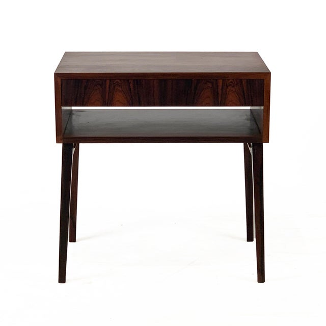 A sleek mid-century design in Brazilian rosewood with a dark patina, gently tapered legs, and a single dove-tailed drawer...