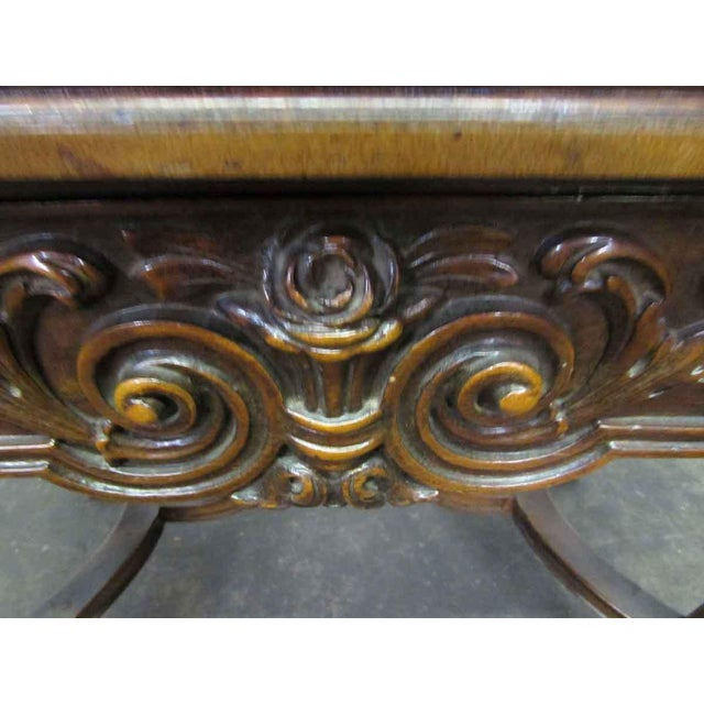 This is an entirely wooden table with extremely detailed ornate carvings on the front molding and legs. There are two...