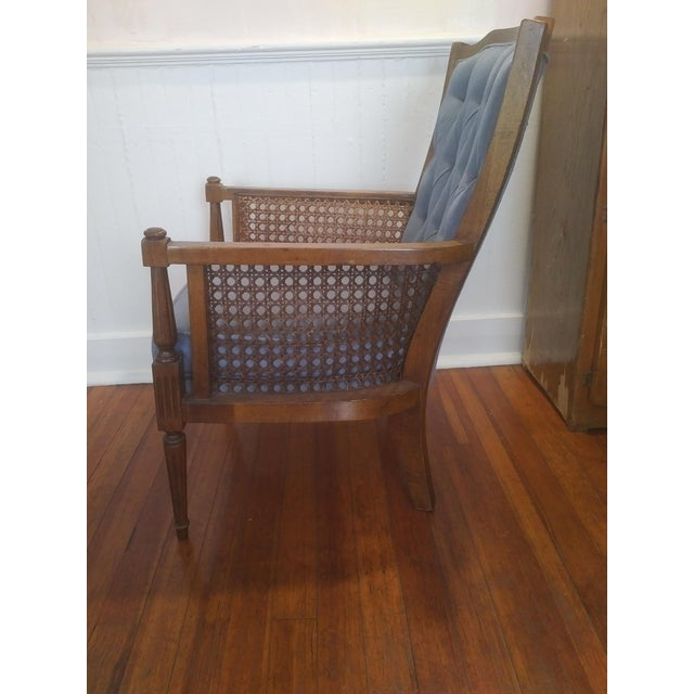 Charming mid-century (with some English regency crossover) wingback chair with caned sides in blue. This is a perfect...