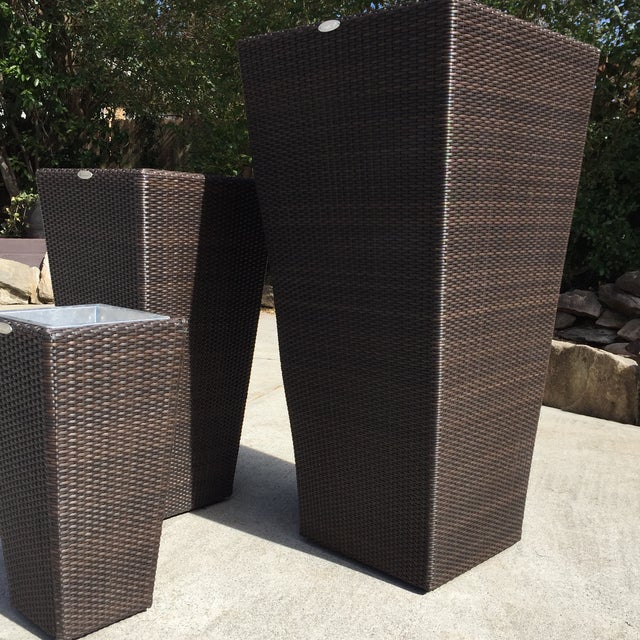 The planters are made of rattan in an espresso finish and are square with a tapered form. Each one has a metal liner to...