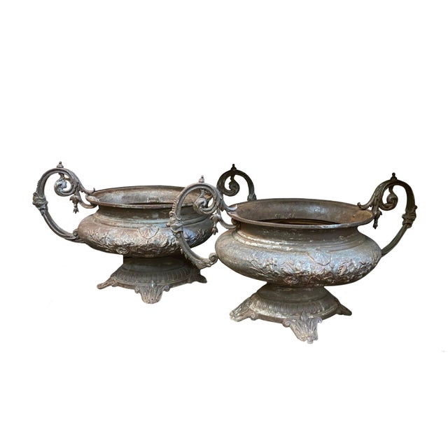 A pair of substantial 19th century cast iron planters with scrolled arms from France.