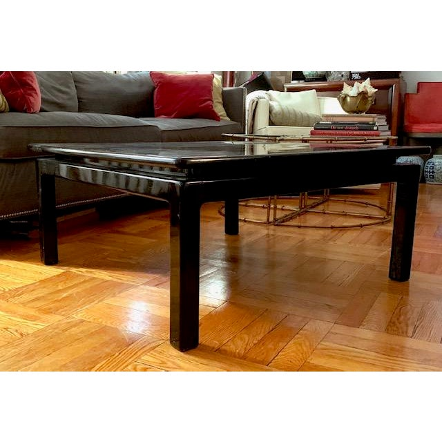 Deep black and lacquered, this all original mid century coffee table is believed to be Italian made. The finish is glossy,...