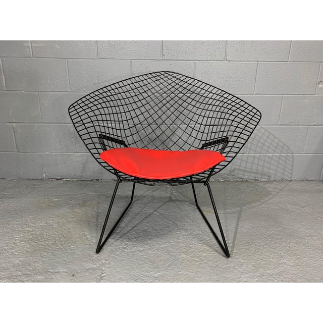 The iconic Diamond Chair by Harry Bertoia for Knoll, originally designed in 1952, in black coated metal and red faux...